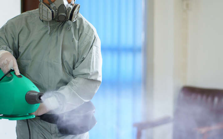 Person in suit spraying disinfectant